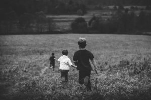 greyscale image of three boys running in a paddock